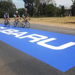 Autocollant rectangulaire géant apposé sur l'asphalte où roulent des cyclistes de compétition