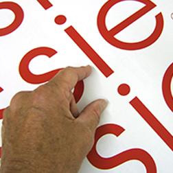 Lettres de vinyle rouges sur fond blanc avec une main les pointant