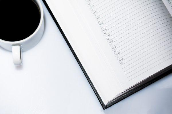 Agenda et café posés sur une table blanche