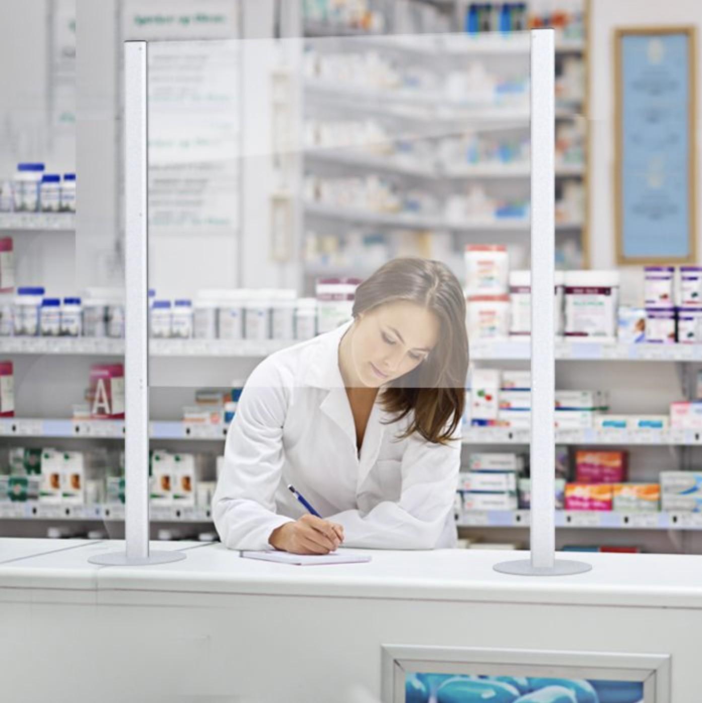 Pharmacienne au comptoir derrière un panneau de plexiglass